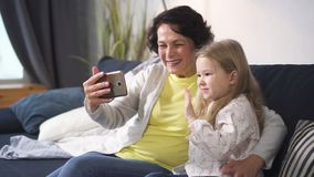 Retired woman and little granddaughter is talking with people by online conference. Cute girl is happy saying hi to family. New modern way of communication stock footage