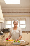 Retired woman looking at the camera in the kitchen Stock Images