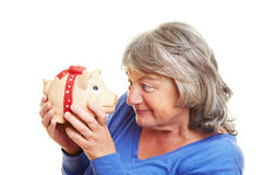 Retired woman looking at piggy bank Stock Photography