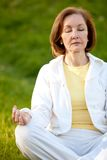 Retired woman practicing yoga Royalty Free Stock Photos