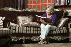 Retired woman reading book Stock Image