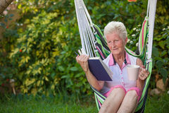 Retired woman reading. Retired healthy senior woman relaxing in garden reading book and drinking coffee royalty free stock photography