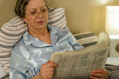 Retired woman reading newspaper before sleeping Stock Photography