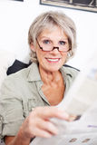 Retired woman reading a newspaper Royalty Free Stock Photos