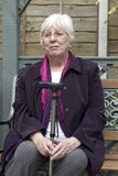 Retired woman sitting. Portrait of an elderly woman sat on a bench taking a rest with walking stick stock photos