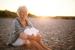Retired woman sitting on the beach. Relaxed retired woman wearing shawl sitting on sandy beach. Old caucasian woman sitting on the beach looking at camera Royalty Free Stock Images