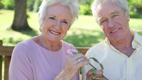 Retired woman smelling a rose with her husband