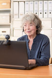Retired woman smiling into webcam Royalty Free Stock Image