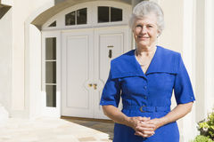 Retired woman standing outside house Royalty Free Stock Images