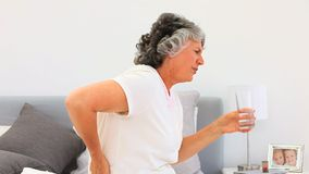 Retired woman taking pills Stock Images