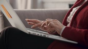 Retired woman typing text on laptop keyboard stock footage