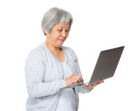 Retired woman use of laptop computer Stock Image