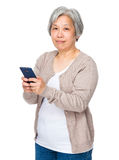 Retired woman use of mobile phone Stock Photography