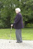 Retired woman walking. Retired elderly woman out walking with the aid of a walking stick royalty free stock photography