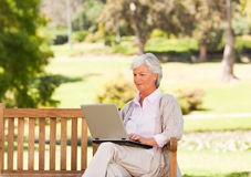 Retired woman working on her laptop. Retired woman in a bench with her laptop Royalty Free Stock Photo