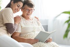 Woman reading book to granddaughter. Retired women wearing glasses reading a book from her youth to her beautiful granddaughter Royalty Free Stock Photos