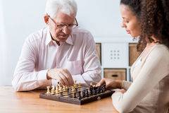 Retiree and caregiver playing chess Stock Image