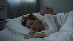 Retiree couple lying in bed awake, woman with her back to man, misunderstanding. Stock footage stock video
