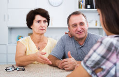 Retiree couple talking with daughter Stock Photos