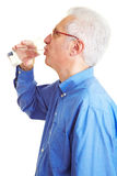 Retiree drinking water. Male senior citizen in blue shirt drinking mineral water Royalty Free Stock Photography
