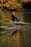 Retiree enjoys Quiet of Lake. Visitor sits alone on the shore of Poplar Tree Lake in Meeman-Shelby Forest State Park near Memphis, Tennessee. Her image and royalty free stock image