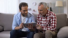 Retiree father and middle aged son scrolling tab, looking and smiling to camera