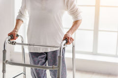 Retiree keeping walking aid and situating near time bucket Stock Photo