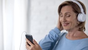 Retiree lady in headphones listening to music on mobile phone and smiling. Stock photo stock photos