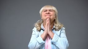 Retiree lady making wish, concept of faith and hope in good news, optimism royalty free stock images