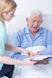 Retiree lying in hospital bed Stock Image