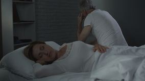 Retiree man sitting on far bed edge backwards, turning to look at sleeping woman. Stock footage stock video footage