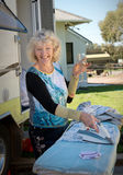 Retiree outside her caravan ironing clothes, enjoying a glass of wine Stock Photography