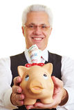 Retiree with piggy bank Stock Images