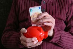 Retiree puts money in the piggy bank stock images