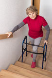 Retiree with walker. Retiree standing with walker in front of a stairway Stock Photography