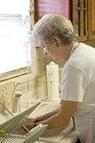 Retiree Washing Dishes In Kitchesn Royalty Free Stock Photo