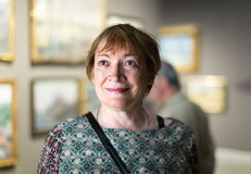 Retiree woman in art museum. Portrait of excited senior woman attentively looking at paintings in art museum Stock Photography