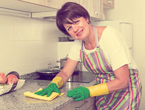 Retiree woman cleaning home Stock Image