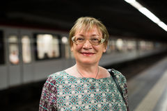 Retiree woman passenger in train station Royalty Free Stock Image