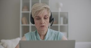 Retiree woman is working from home in call-center, phone sales and tech support department, remote job, distant work for