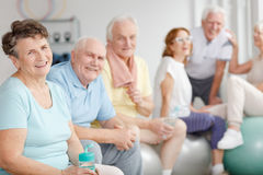 Retirees spending time together. Happy active retirees spending time together at the gym stock photography