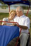 Retirement. Happy senior couple sitting on a bike in a park Royalty Free Stock Photos