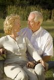 Retirement. Happy senior couple sitting in a park Stock Photo