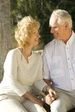 Retirement. Happy senior couple sitting in a park Royalty Free Stock Photos