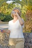 Retirement. Happy senior woman drinking water after a walk stock photo