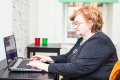 Retirement age woman sitting at table with a laptop on the table Stock Photos
