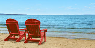 Retirement Aspirations. And financial planning symbol with two empty blue adirondack chairs sitting on a tropical sandy beach with ocean view as a business Stock Photo