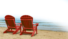 Retirement Aspirations. And financial planning symbol with two empty blue adirondack chairs sitting on a tropical sandy beach with ocean view as a business Royalty Free Stock Image