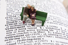 Retirement definition. Miniature elderly couple sitting on bench with retirement definition Stock Photos