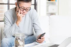 Retirement financial planning. Mature 50s Asian man doing analysis on his spending, looking on data chart and smart phone. Saving, retirement, retirees financial Stock Images